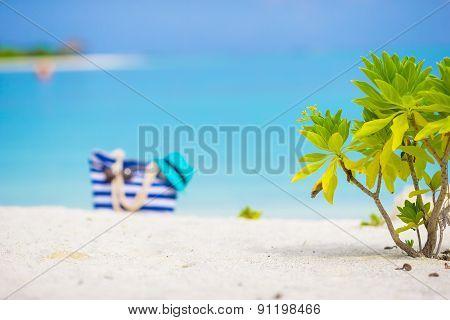Beach accessories - blue bag, straw hat, sunglasses on white beach
