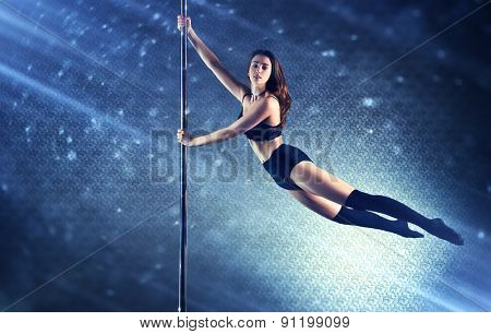 Young slim pole dance woman flying on pole. Special light rays and spots motion effect.