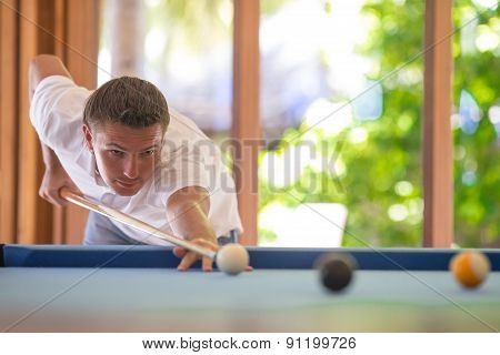 Young man playing billiards on summer vacation