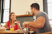 picture of breakfast  - Shot of cheerful young couple having breakfast in kitchen at home - JPG