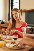 foto of breakfast  - Portrait of attractive young woman sitting at breakfast table eating and looking at camera - JPG