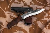 image of crossed pistols  - Makarov pistol the crossed with a knife on the background of desert camouflage - JPG