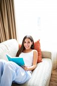 picture of recliner  - Woman reclining against orange cushion on couch with open book on lap looking up smiling - JPG