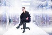 stock photo of thoughtfulness  - Thoughtful businessman sitting on a swivel chair against server room with towers - JPG