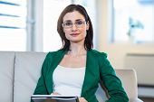 stock photo of psychologist  - Psychologist sitting on the couch and looking at camera in the office - JPG