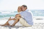stock photo of couple sitting beach  - Senior Couple On Holiday Sitting On Sandy Beach - JPG