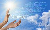foto of miracle  - Pair of female hands outstretched into a blue sky background with a word cloud of Miracle related words streaming across to the right and a bright sun burst on the left - JPG