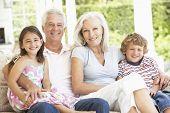 pic of grandparent child  - Grandparents And Grandchildren Sitting On Cane Sofa At Home - JPG