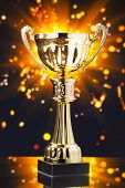 picture of trophy  - gold cup trophy against shiny sparks background - JPG