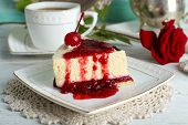 image of cheesecake  - Tasty piece of cheesecake with berry sauce on plate on table close up - JPG