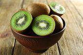 stock photo of fruit bowl  - Juicy kiwi fruit in bowl on wooden background - JPG