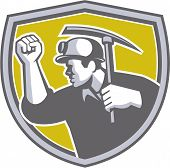 picture of clenched fist  - Illustration of a coal miner wearing hardhat wiith clenched fist holding pick axe viewed from the side set inside shield crest on isolated background done in retro style - JPG