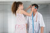 stock photo of obstetric  - Young girl measures the size of the head of a male doctor - JPG