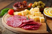 stock photo of antipasto  - Antipasto catering platter with salami and cheese on a wooden background - JPG