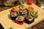 picture of na  - Delicious sauced Saka na maki sushi rolls served with a wood plate - JPG