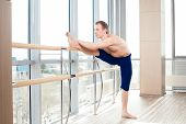 foto of ballet barre  - in the hall man doing stretching near Barre - JPG