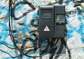 image of electricity meter  - Old electric meter with wires on the painted stone wall - JPG
