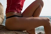 picture of string bikini  - Sexy girl in sportswear and tanga string sitting on the cliff of the rocky beach - JPG