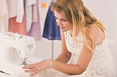 pic of dress-making  - Young woman making a dress at her office - JPG