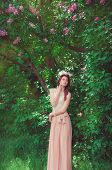 stock photo of lilac bush  - Young beautiful girl in a long dress and a wreath of flowers in the garden of lilac bush - JPG
