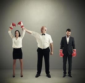 stock photo of referee  - referee holding winner businesswoman in boxer gloves and looking at her - JPG