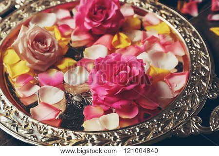 Pink and yellow rose petals in silver bowl, close up