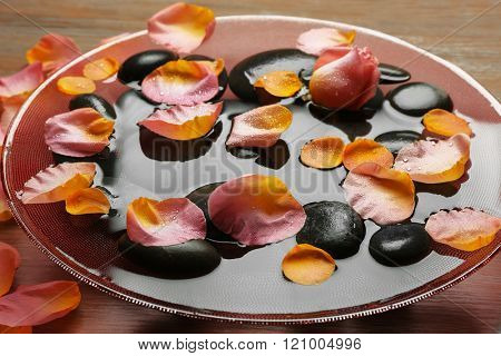 Pink and yellow rose petals in glass bowl with water and black stones on wooden background
