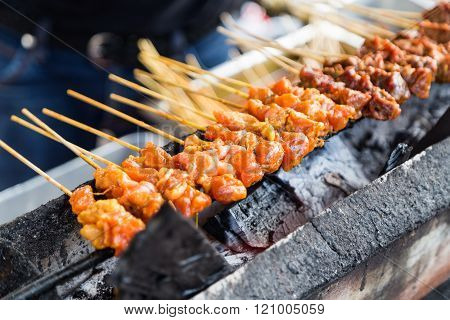 Vendor preparing chicken and beef barbecue satay on charcoal grille