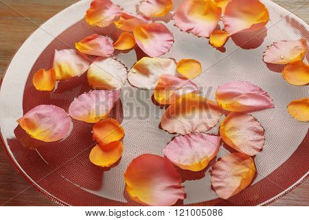 Pink and yellow rose petals in glass bowl with water on wooden background