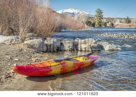whitewater kayak with a paddle on a river shore  - Arkansas River at Big Bend near Poncha Springs, Colorado in winter scenery