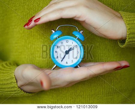 Little Blue Alarm Clock In The Hands Of Woman