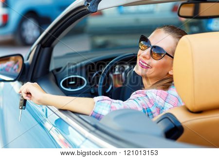 Young Pretty Woman In Sunglasses Sitting In A Convertible Car With The Keys In Hand