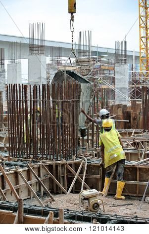 SELANGOR, MALAYSIA - DECEMBER 12, 2015: A group of construction workers pouring concrete using concrete bucket into the ground beam form work at the construction site.