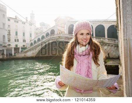 Woman Tourist With Map Near Rialto Bridge Looking Into Distance