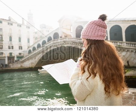 Woman Tourist With Map Near Rialto Bridge. Seen From Behind