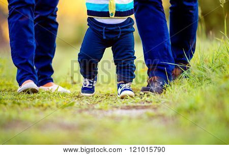 Legs of mother, father, their son making first steps