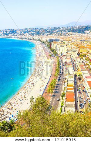 NICE, FRANCE - AUGUST 10, 2012: Tourists enjoy the good weather at the beach in Nice, France. The beach and the waterfront avenue, Promenade des Anglais, are full almost all the year.