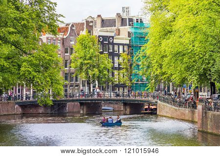 AMSTERDAM, NETHERLANDS - SEPTEMBER 3, 2012: Tourists sailing on a canal in Amsterdam. Amsterdam is the capital of the Netherlands and the canals and harbours fill a full quarter of the city surface.