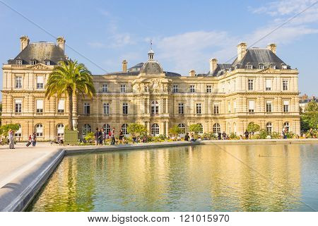 PARIS, FRANCE - SEPTEMBER 20, 2012: People walking in the Luxembourg Garden. Located in the Quartier Latin, the Palais du Luxembourg is part of the garden and the upper house of the French Parliament.