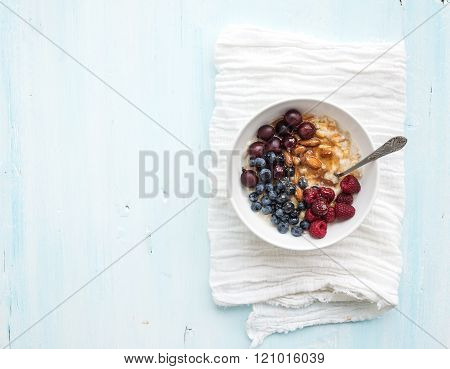 Healthy breakfast set. Bowl of oat porridge with fresh berries, almond and honey over white napkin. Top view, light blue backdrop