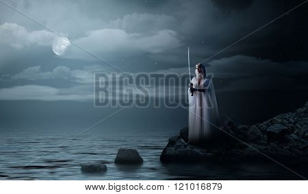 Young elven girl with sword at night sea shore