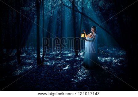 Young elven girl with lantern at night forest