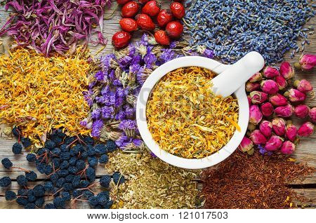 Mortar of dry marigold flowers healthy herbs herbal tea assortment and berries on old wooden table. Herbal medicine.