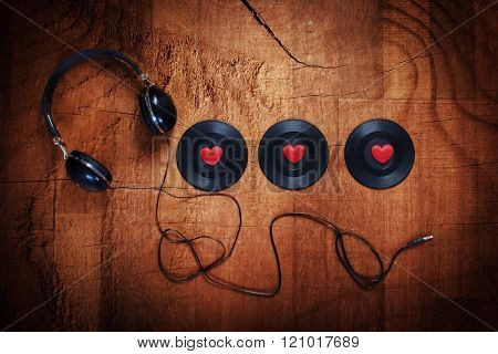Three black vinyl records with red love hearts and a set of headphones on a rough wooden background