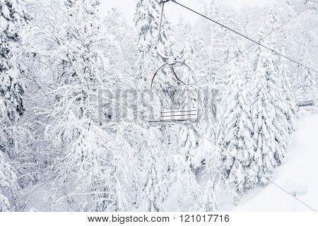 Old cable ski lift with no passengers going across the coniferous forest in 'Kolasin 1450' mountain ski resort near the town of Kolasin in Montenegro after a heavy snowfall on a winter day