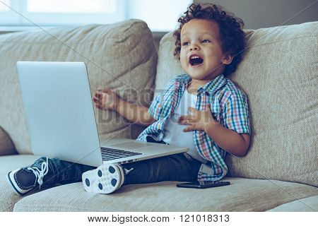 Mom how does this thing turns on?Little African baby boy keeping mouth open while sitting on the couch at home with laptop on his knees