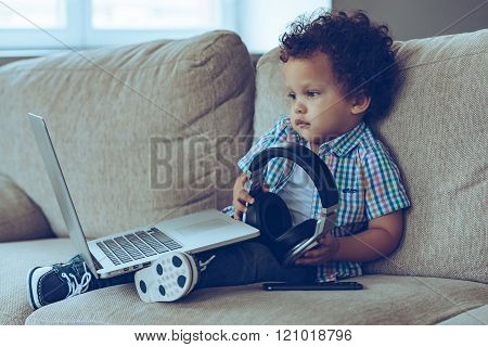 Technologies make life easier. Side view of little African baby boy looking at laptop and holding headphones while sitting on the couch at home