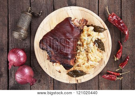 Roasted pork knuckle served with sauerkraut on wooden table