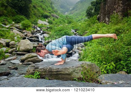 Young sporty fit woman doing yoga asana Eka Pada Koundinyasana 1 at tropical waterfall