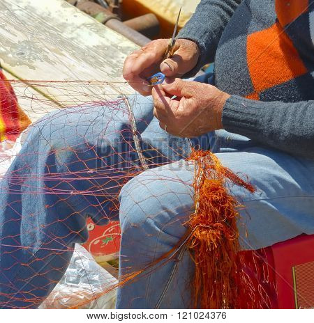Fisherman is repairing the fishnet. Close uo hands